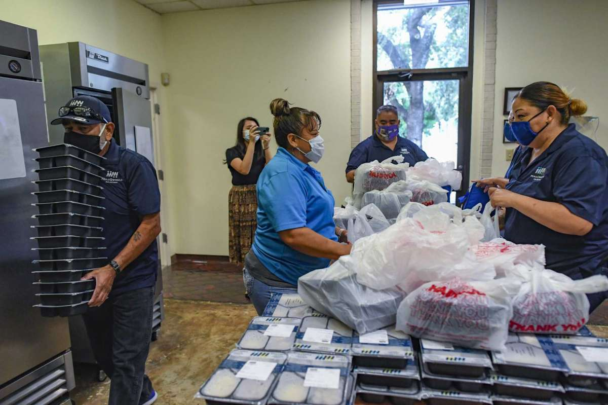 Delivery drivers pack bags at Meals on Wheels for delivery to area seniors on Aug. 10, 2021.